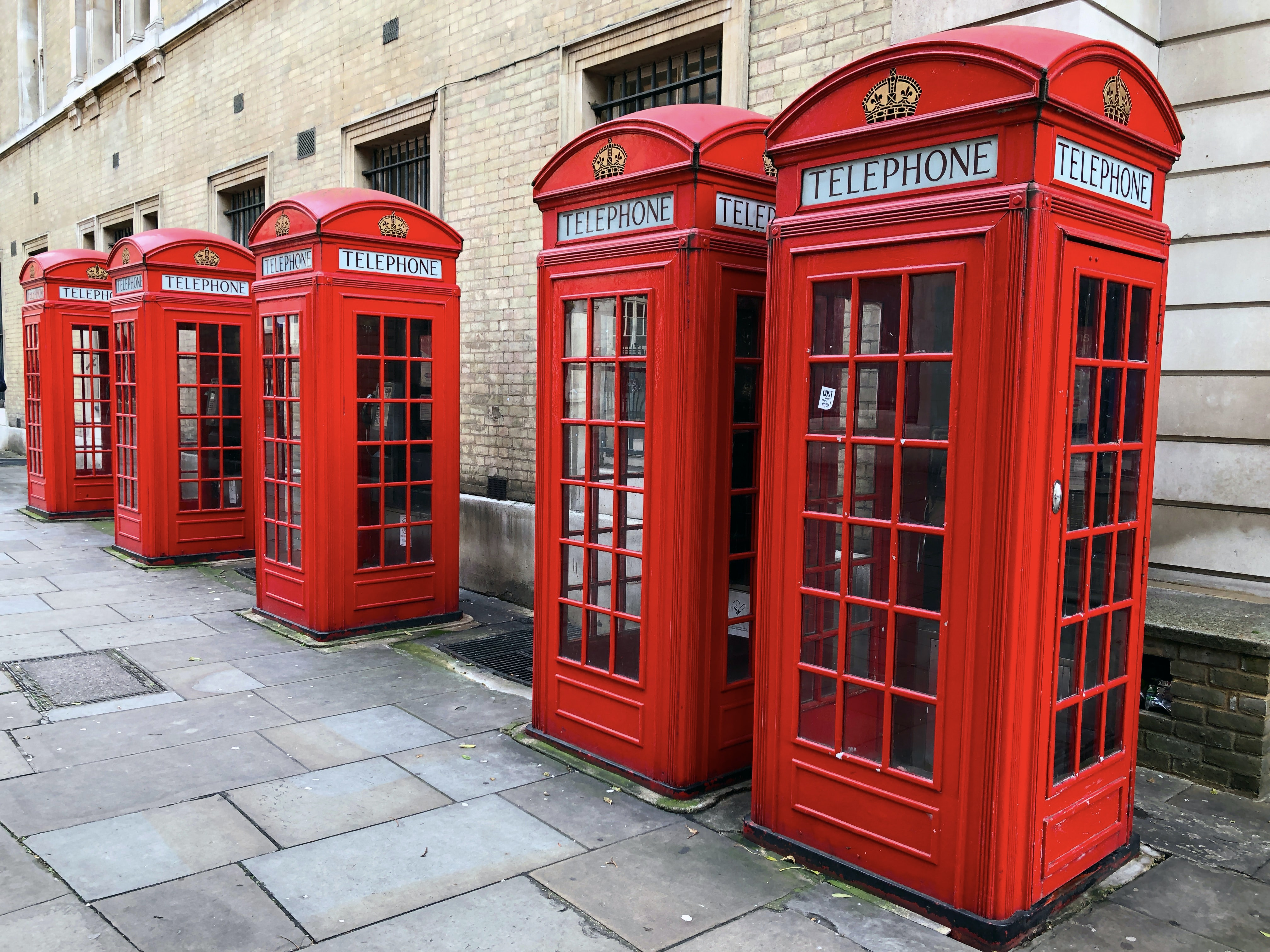 lined-up red telephone booths near building