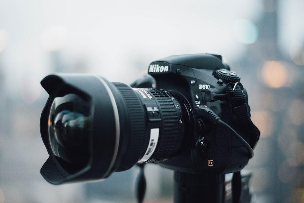 black Nikon D810 camera standing on black metal tripod stand at daytime