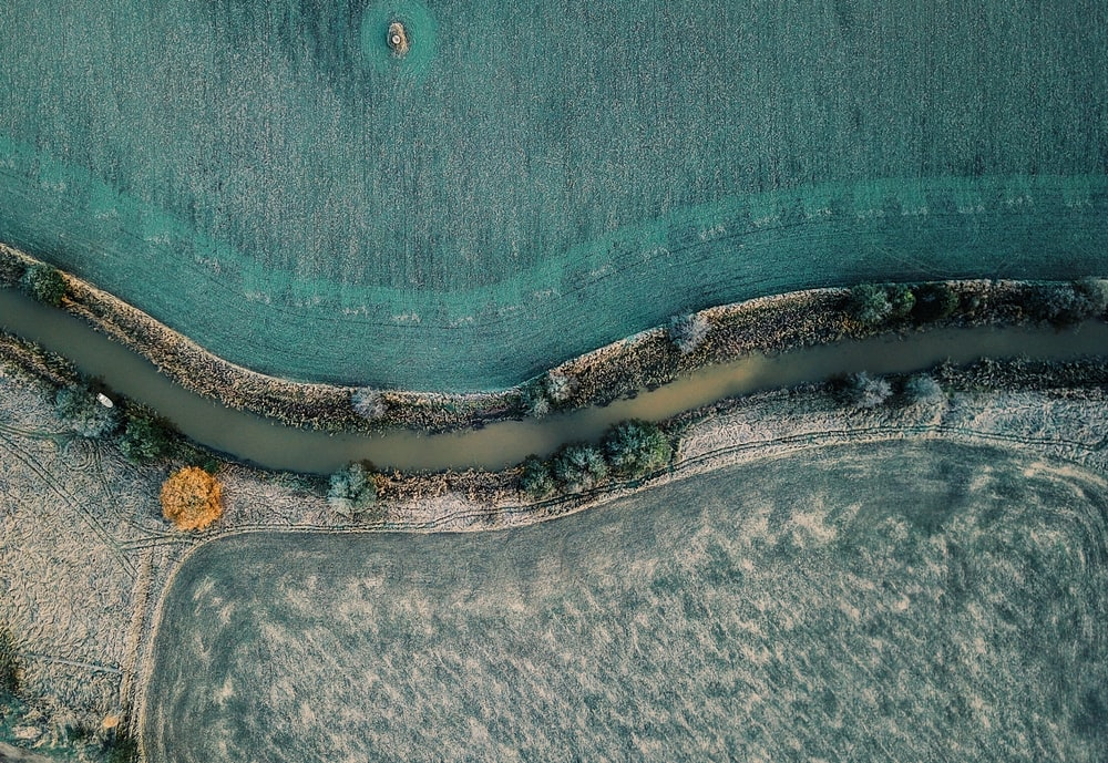 areal photography of river between grass fields