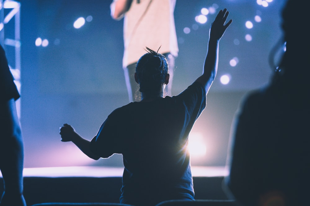 woman waving hands towards person performing on stage