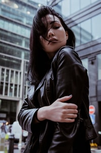 selective focus photography of woman wearing black leather zip-up jacket