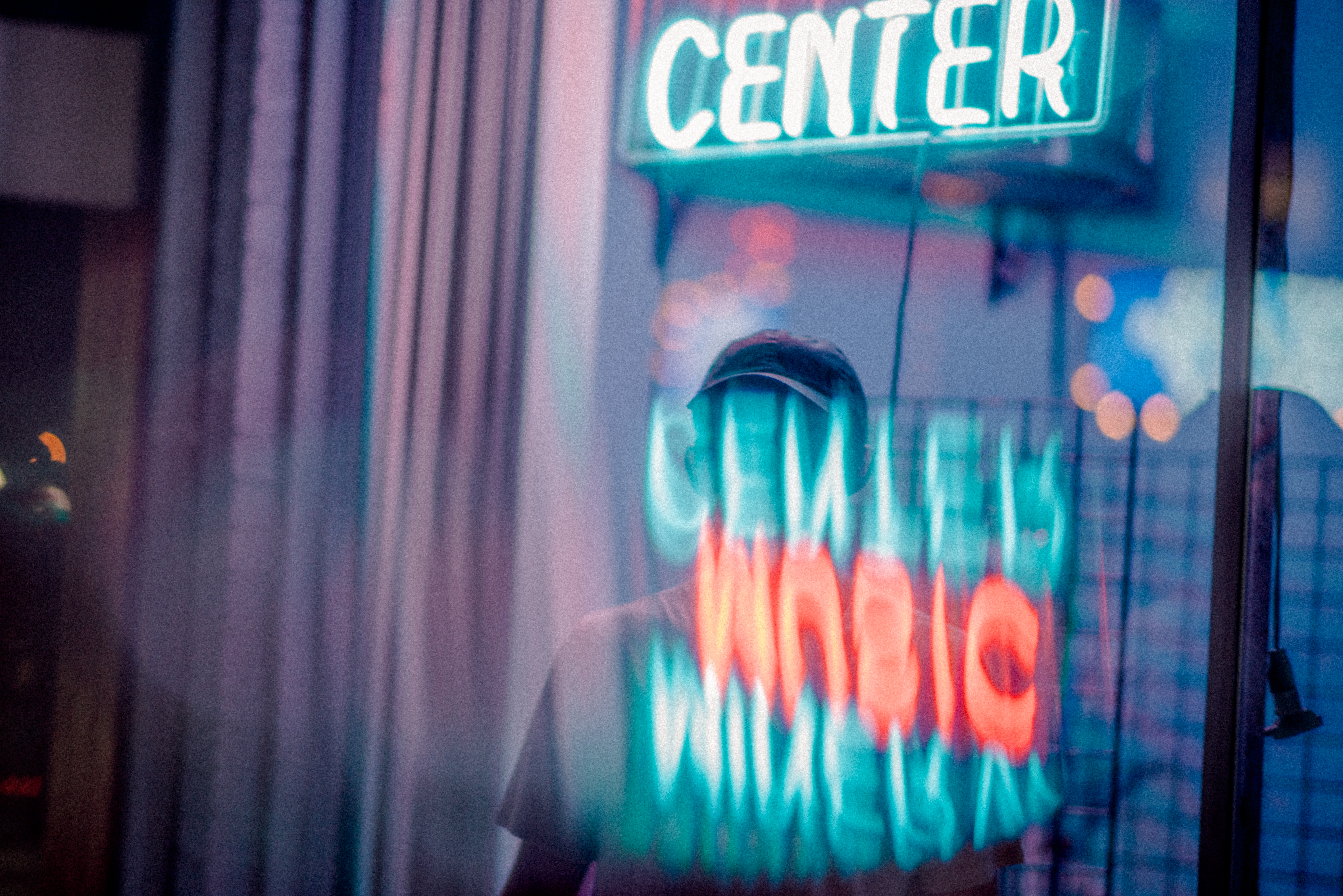turned on green Center neon signage behind clear glass wall