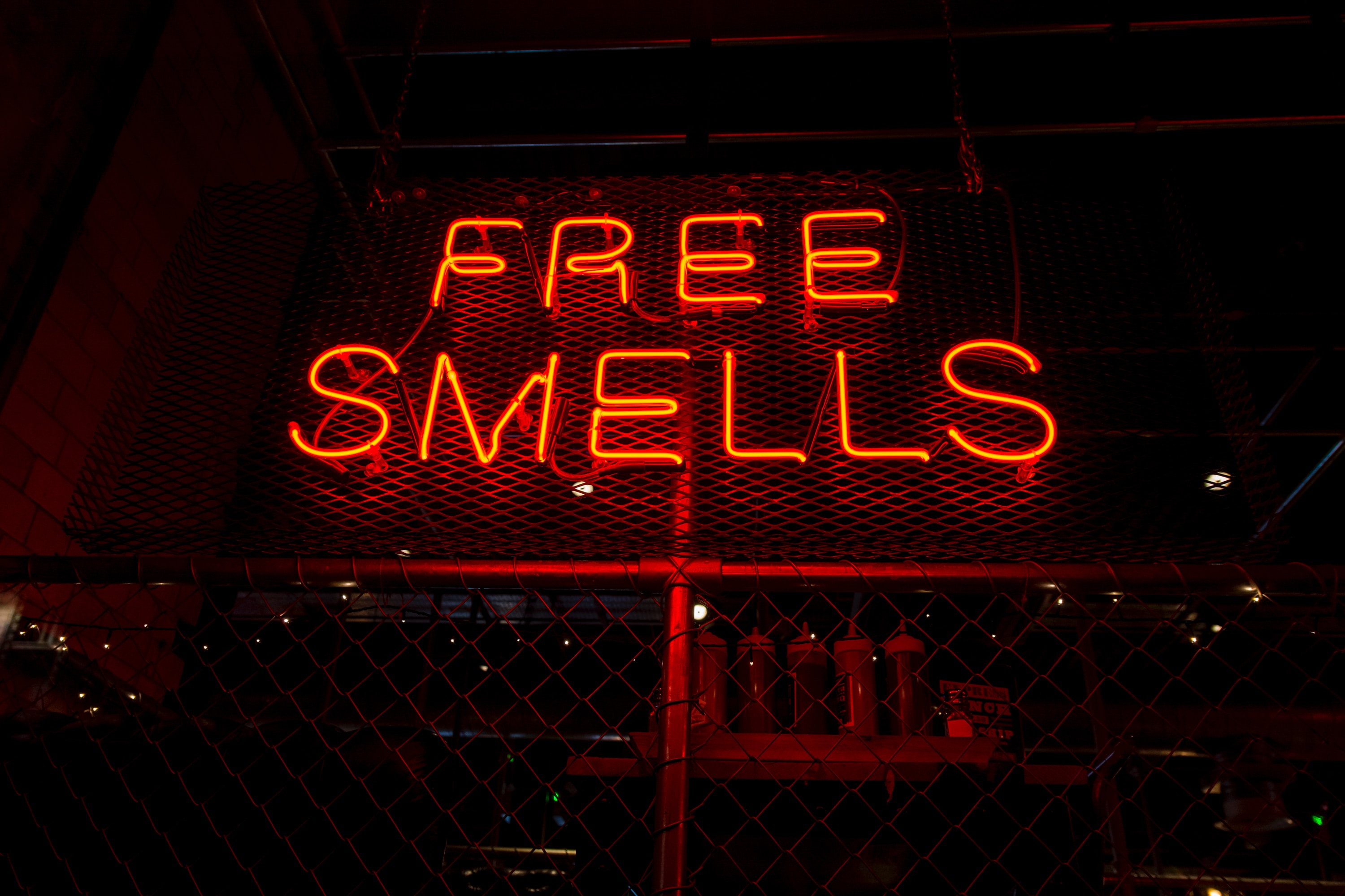 """Red sign in the night which says """"free smells"""""""