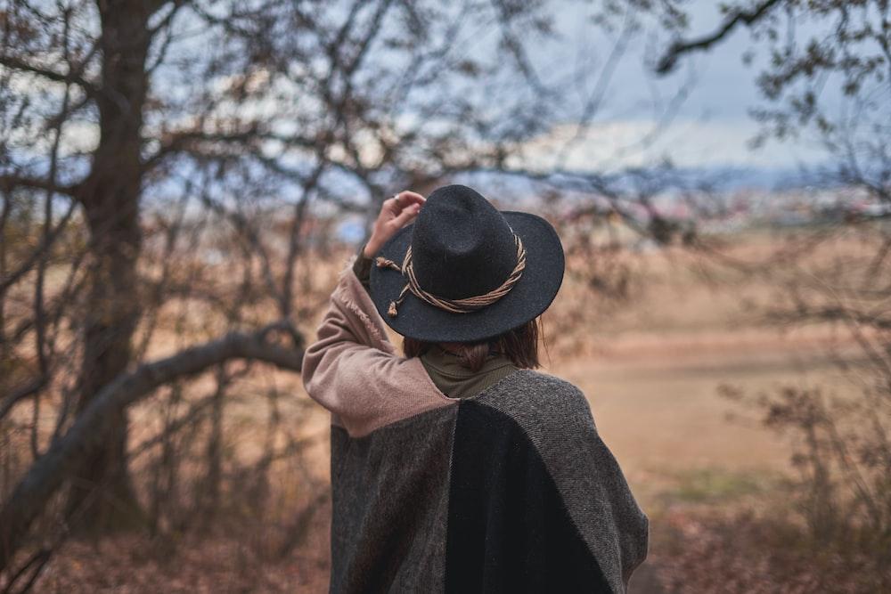woman wearing black hat standing near green trees
