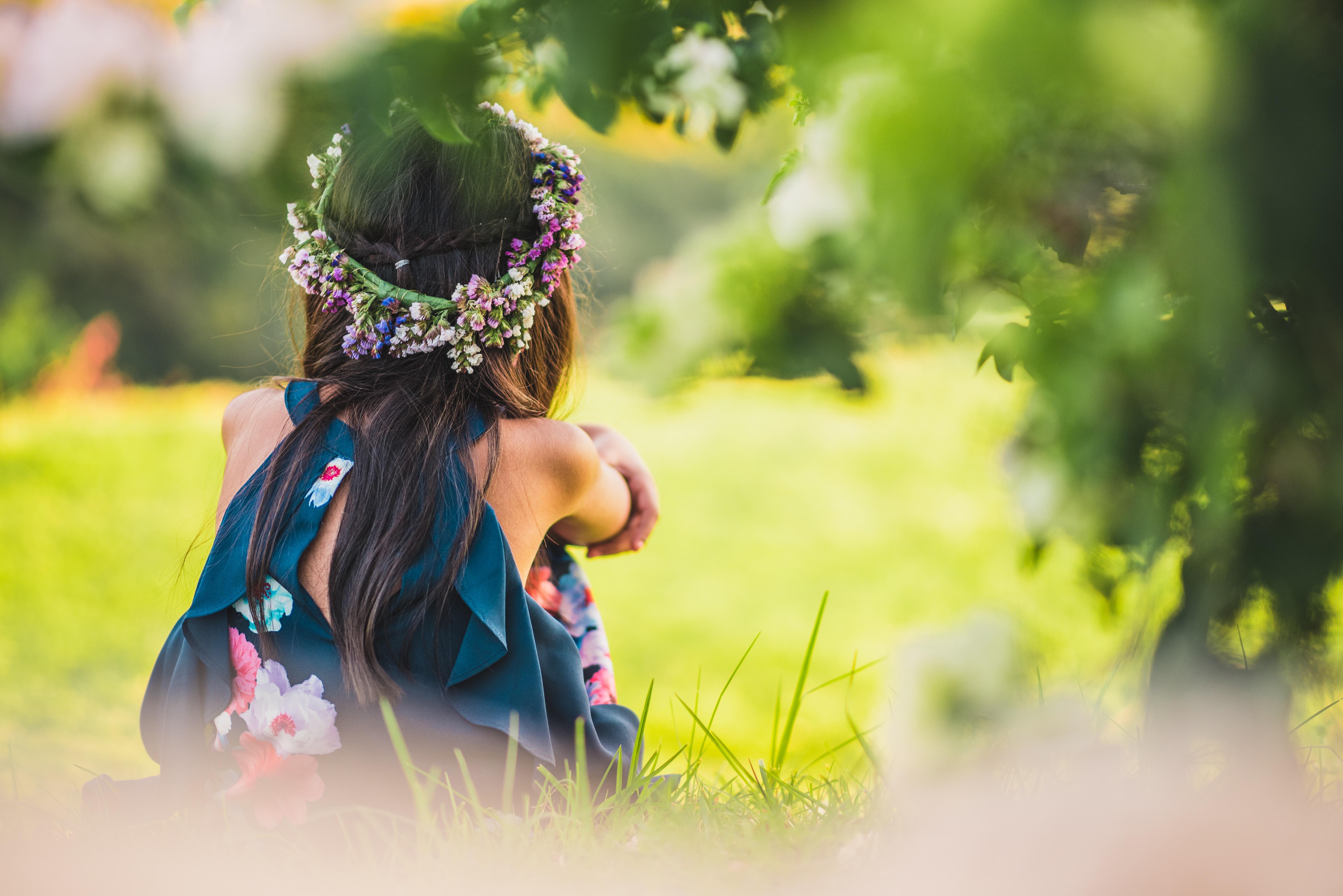 girl wearing blue floral dress sitting near green grass during daytime