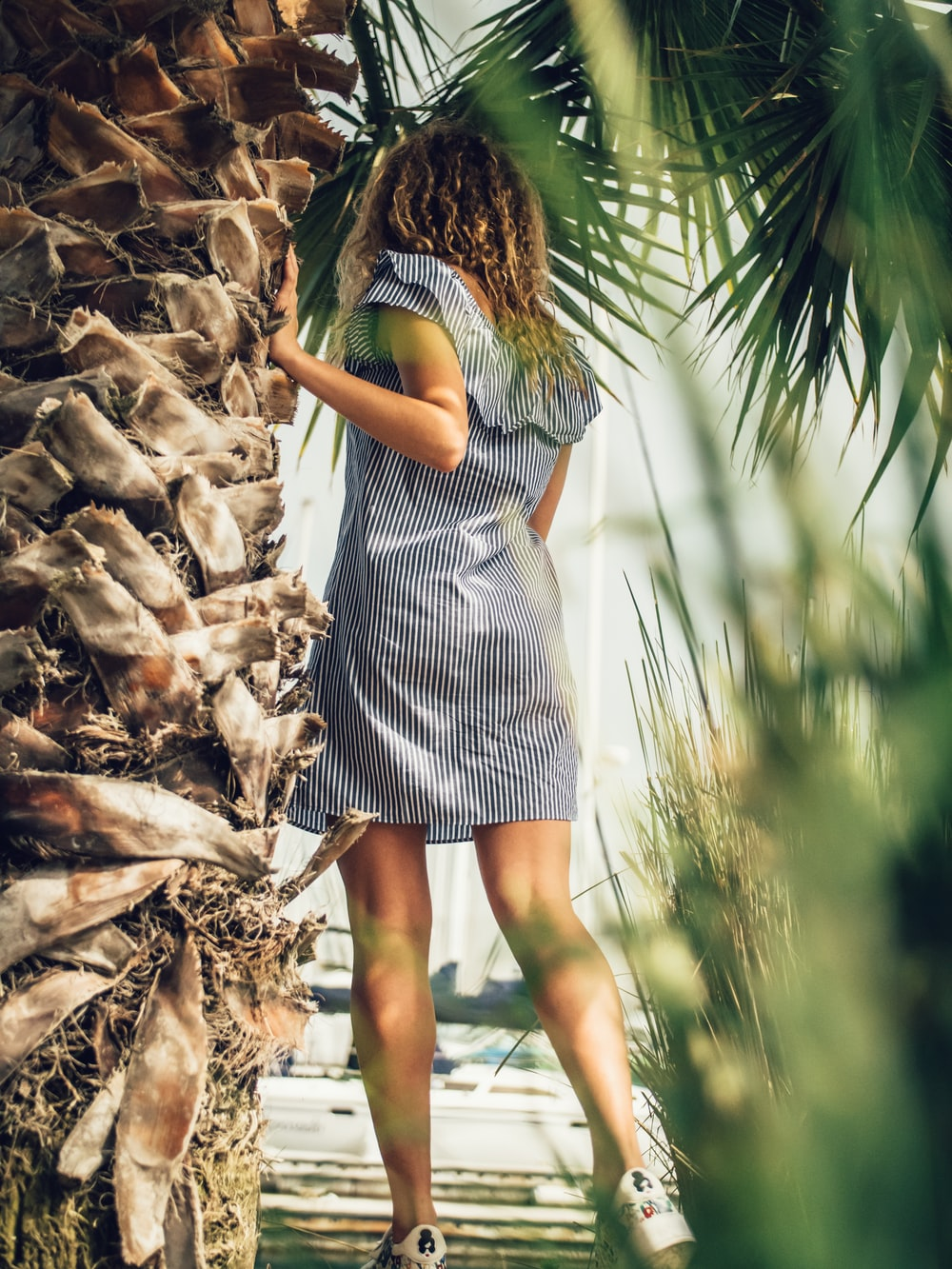 photo of woman standing beside palm tree