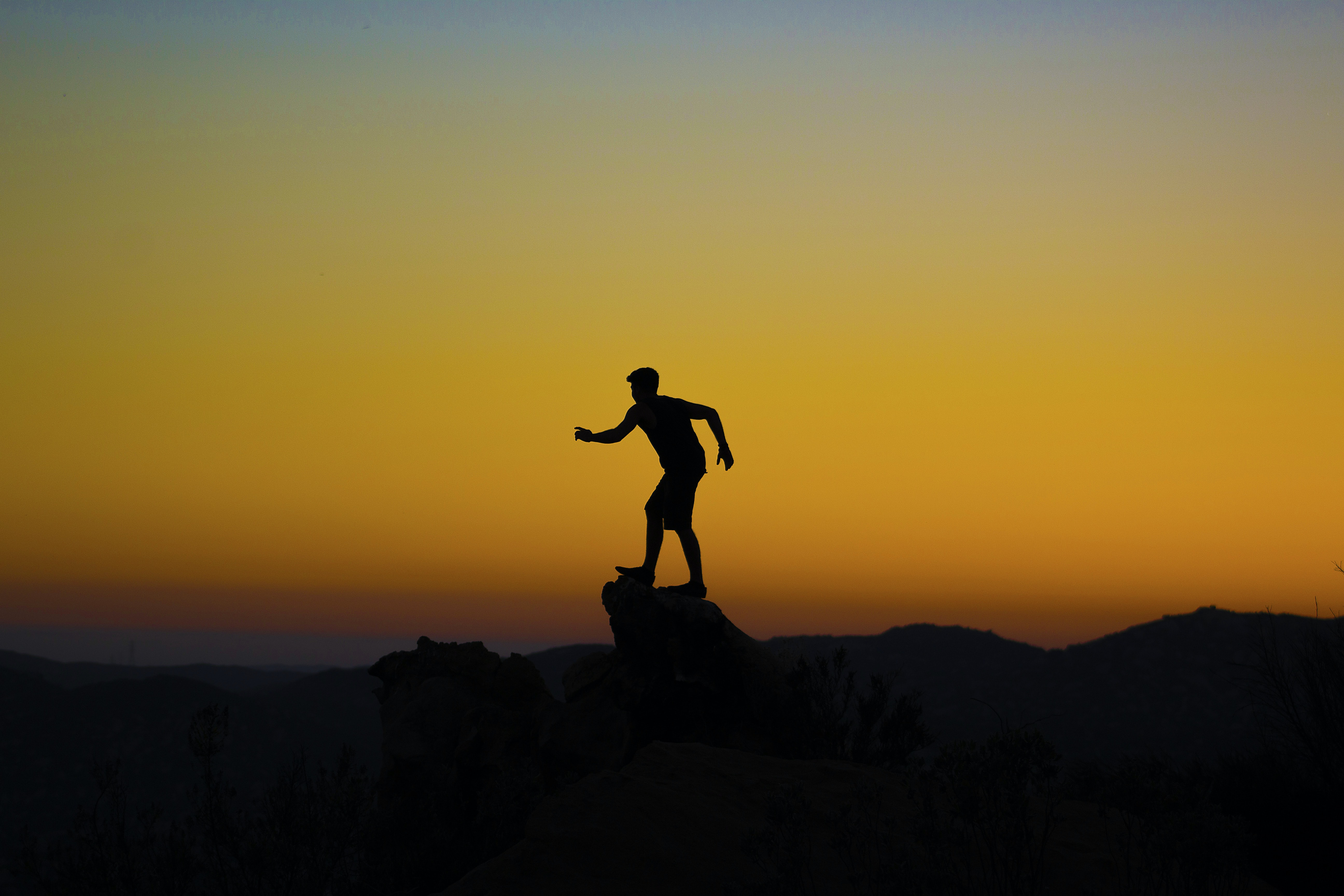 silhouette photo of person on mountain cliff