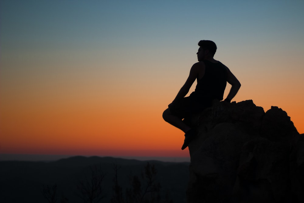silhouette of man sitting at rocks
