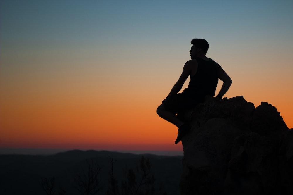 silhouette of man sitting at rocks