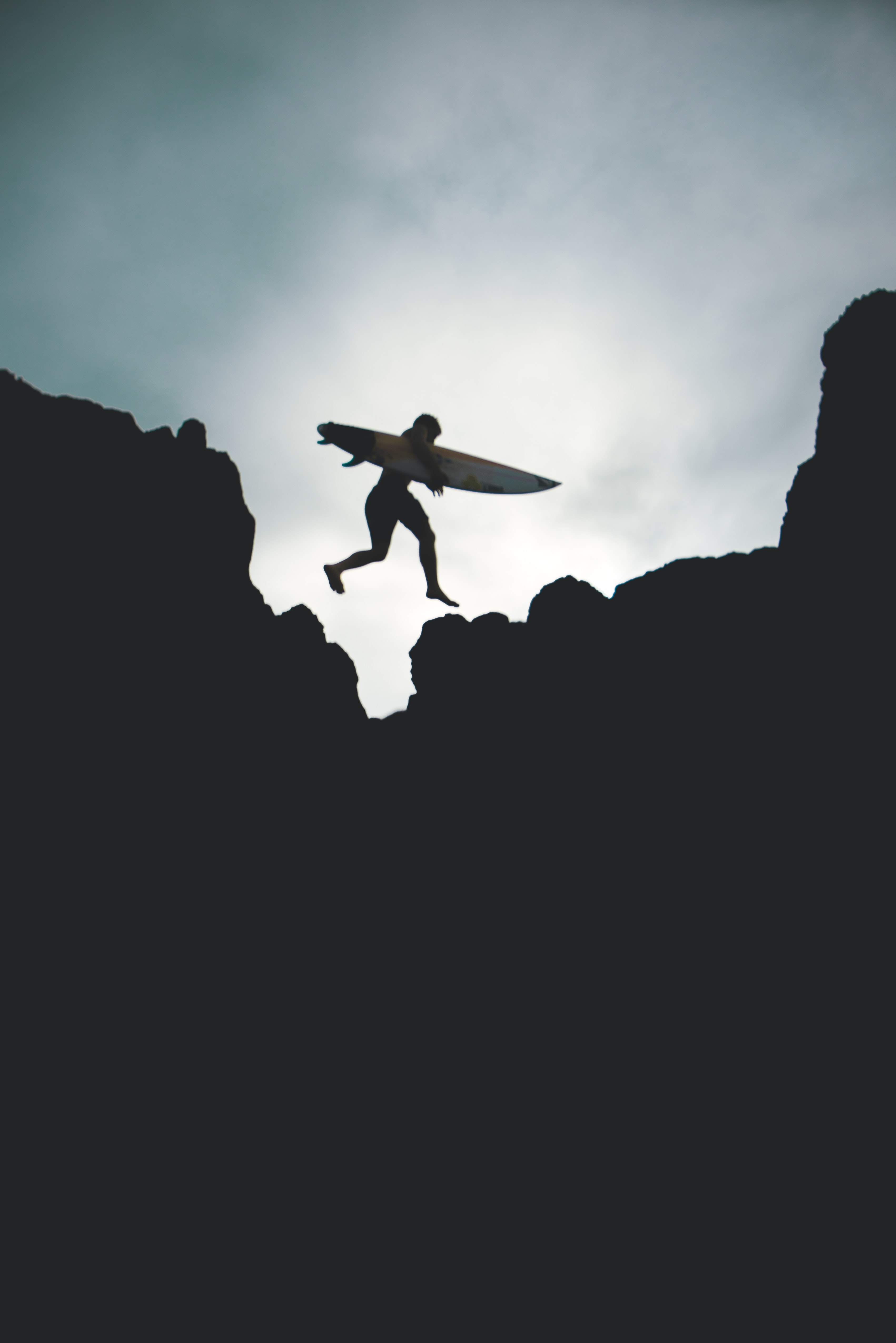 silhouette photo of man jumping on big rock holding surfboard
