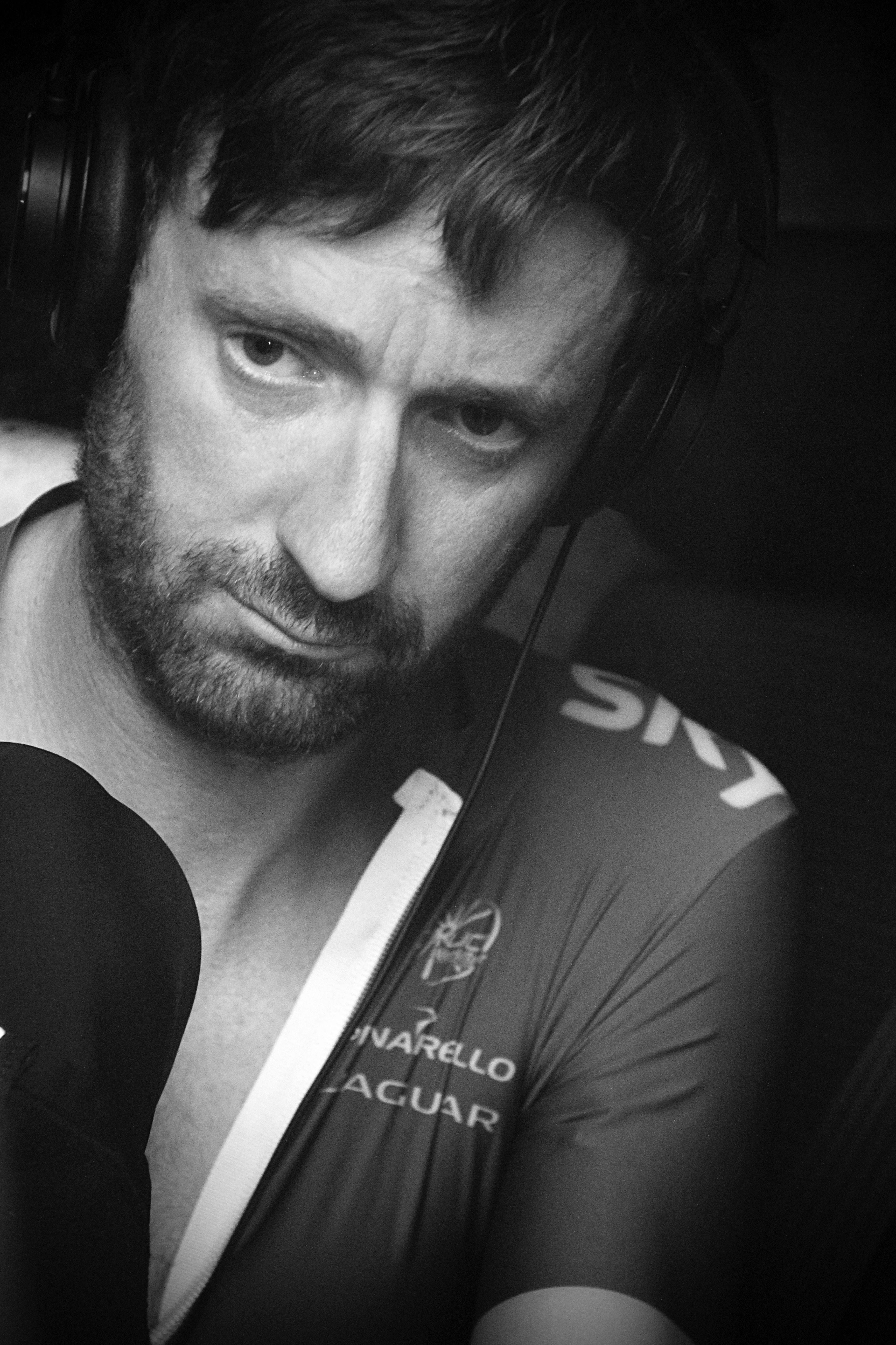 grayscale photo of man wearing corded headphones