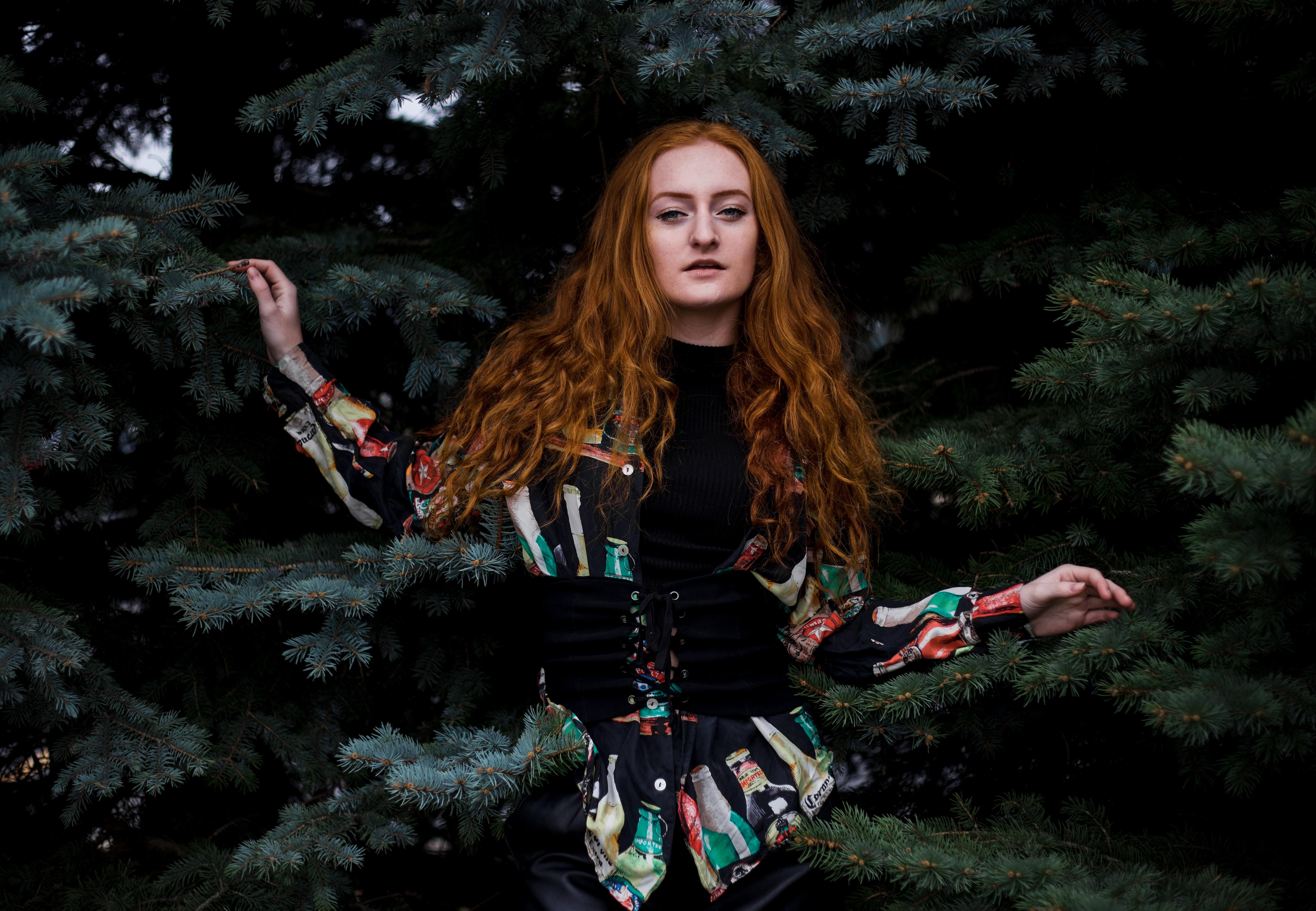 woman in black long-sleeved top beside trees