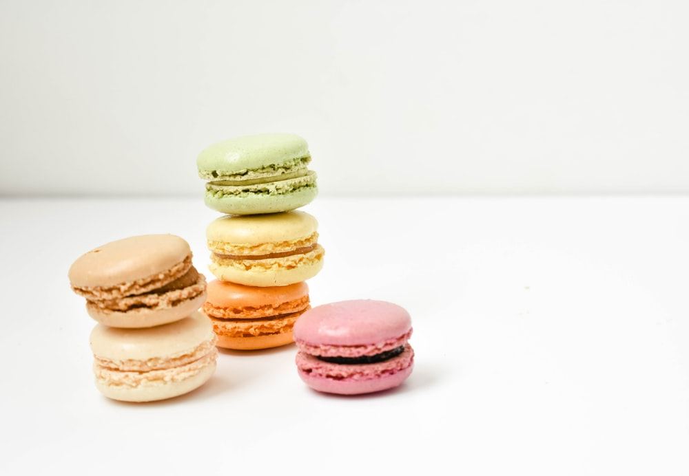 five macaroons on white surface