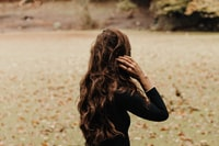 brown haired woman holding her hair during daytime