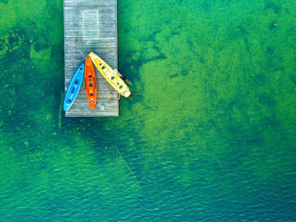 bird's eye photography of red, blue, and yellow kayaks on wooden dock near body of water