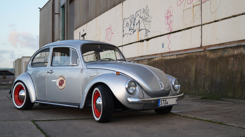silver Volkswagen Beetle near white and brown wall during daytime