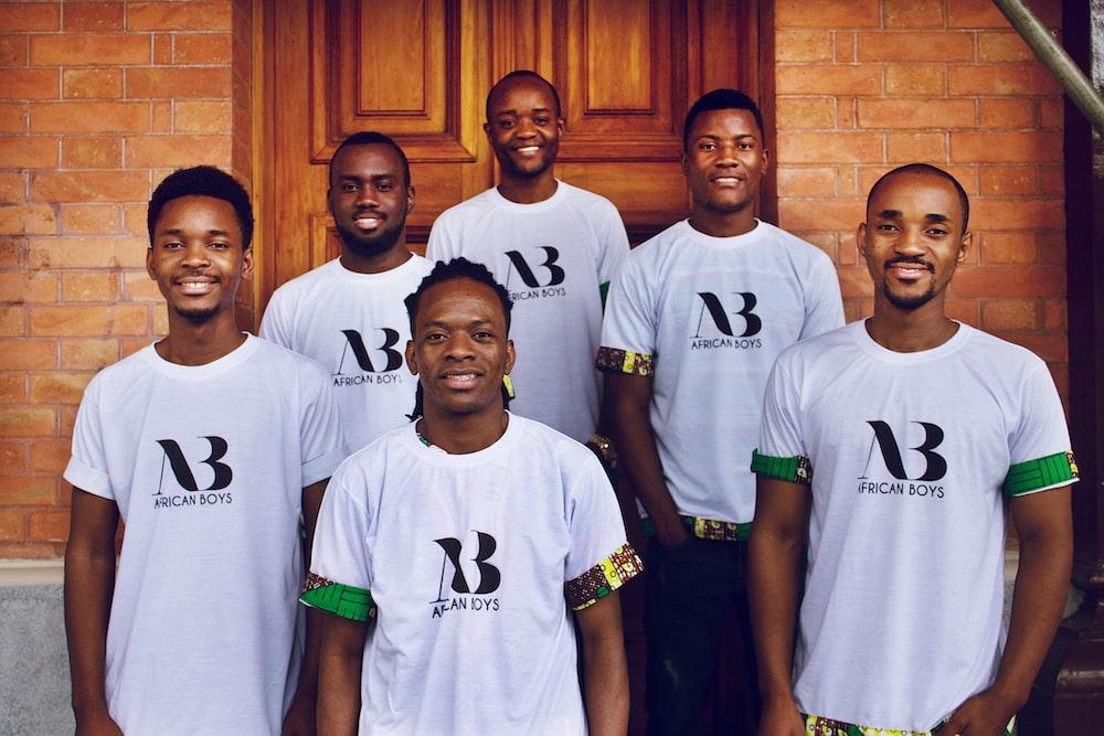 group of men standing near brown wooden door