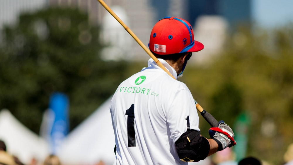 man wearing white and black 1 jersey shirt holding brown and black stick