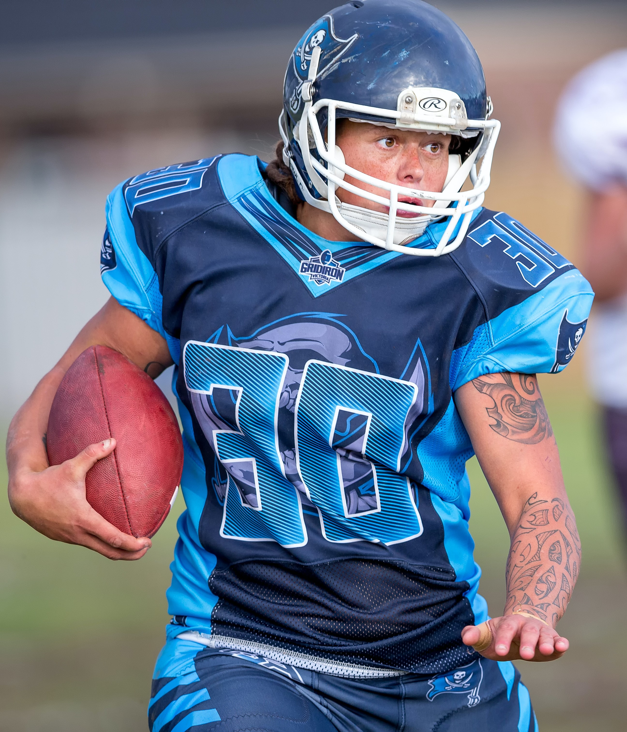 focus photo of person playing football holding ball while running