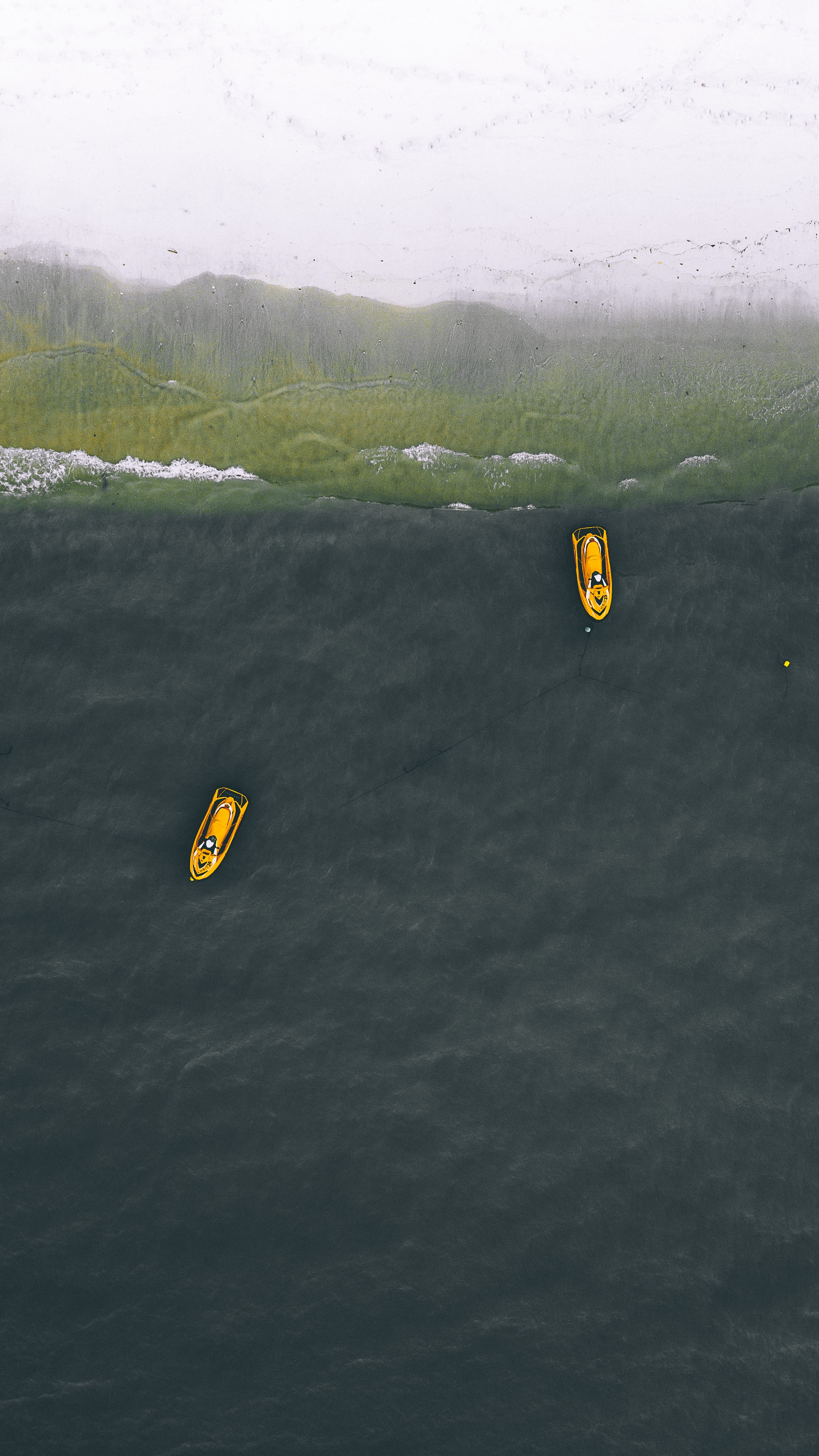 two yellow personal watercraft on water