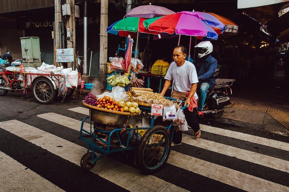 man pushing his food cart on pedestrian lane during daytime