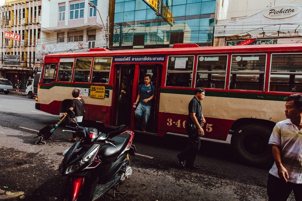 people walking down on red bus during daytime