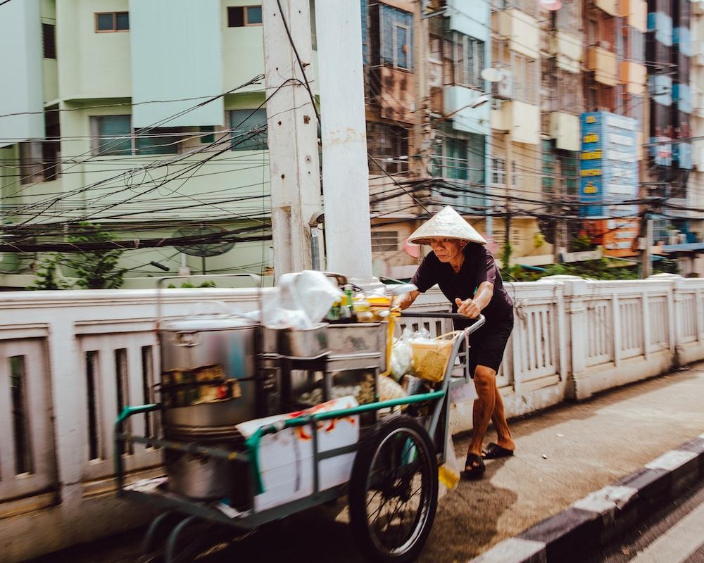 man pushing the cart on street