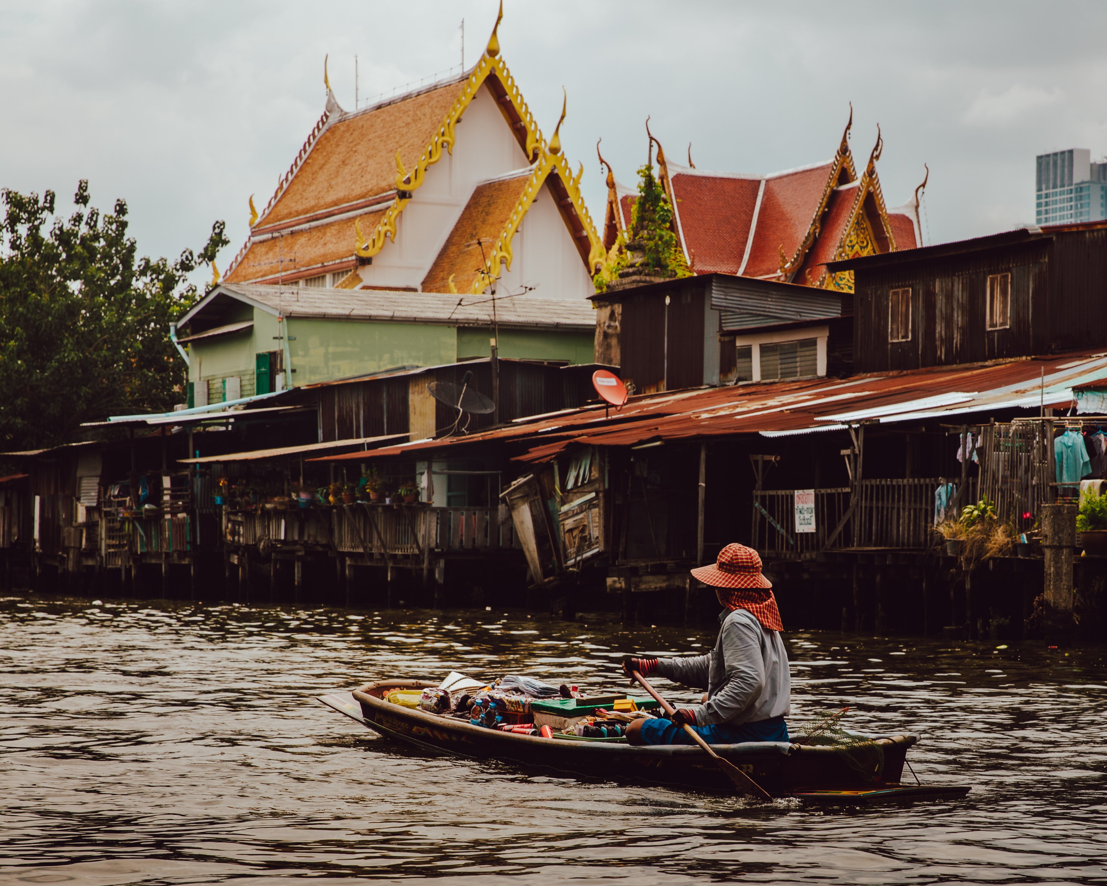 woman riding boat holding paddle on calm body of water in front of houses