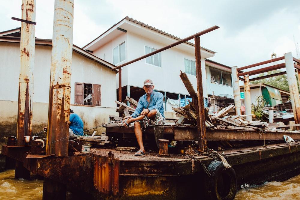 man wearing blue shirt sitting near brown metal while fishing during daytime