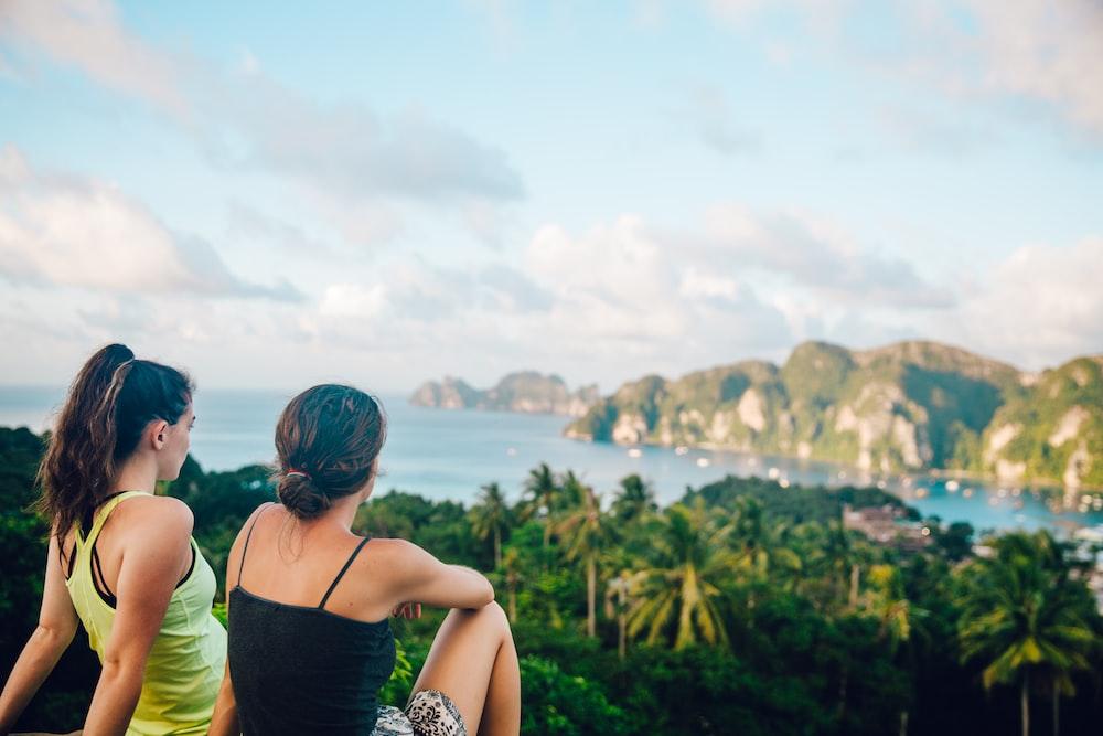 two women sitting on hilltop