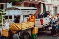 monk on front of food kiosk near pickup truck