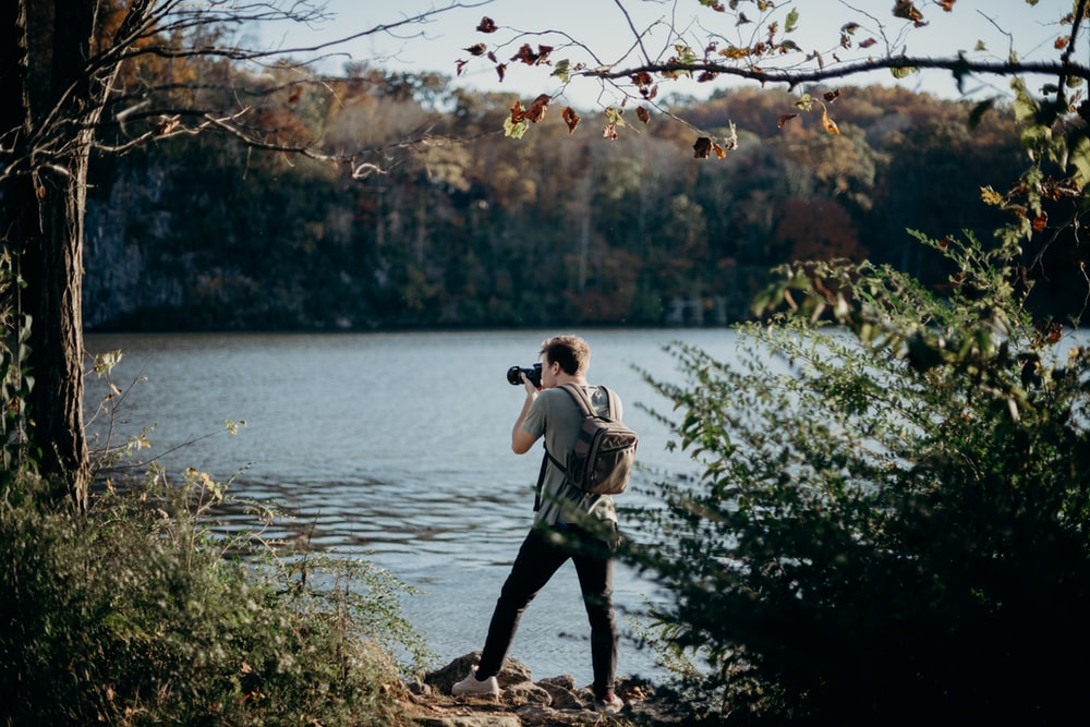 man with backpack taking picture beside lake