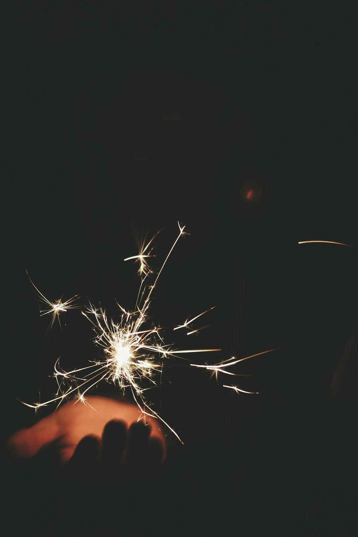 person hand bellow sparkling light