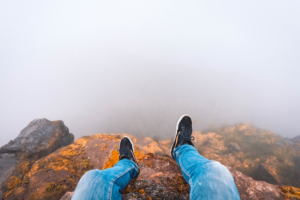 person wearing blue denim jeans sitting on brown wooden rock looking down on mist