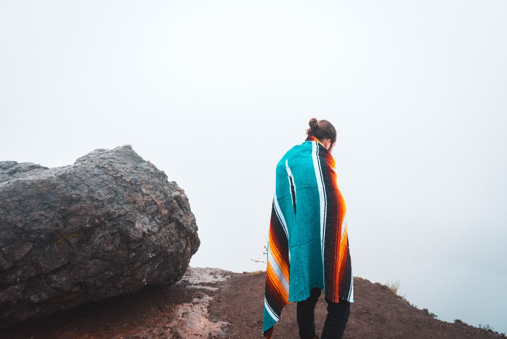person standing beside black stone covering body of blanket