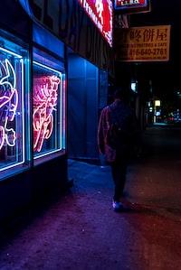 man walking beside neon-lighted store taken at nigthttime