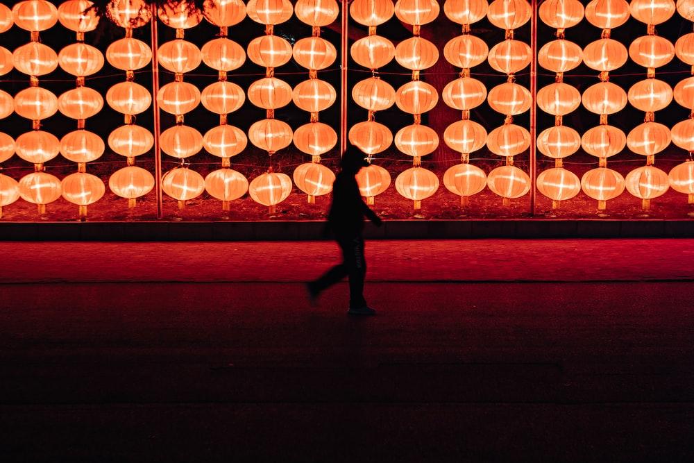 silhouette of person walking near lantern lamp