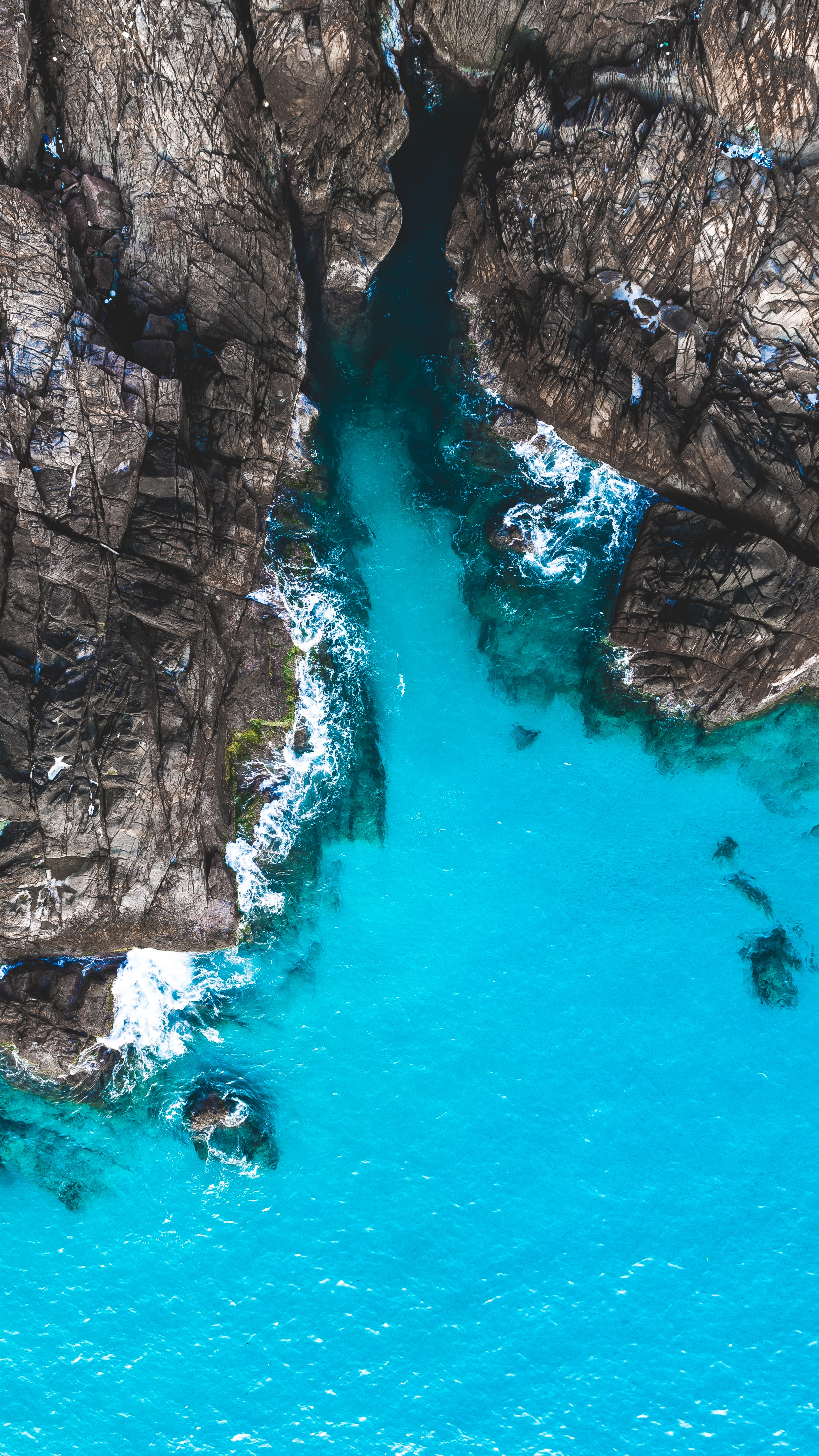 aerial photography of body of water beside cliff during day
