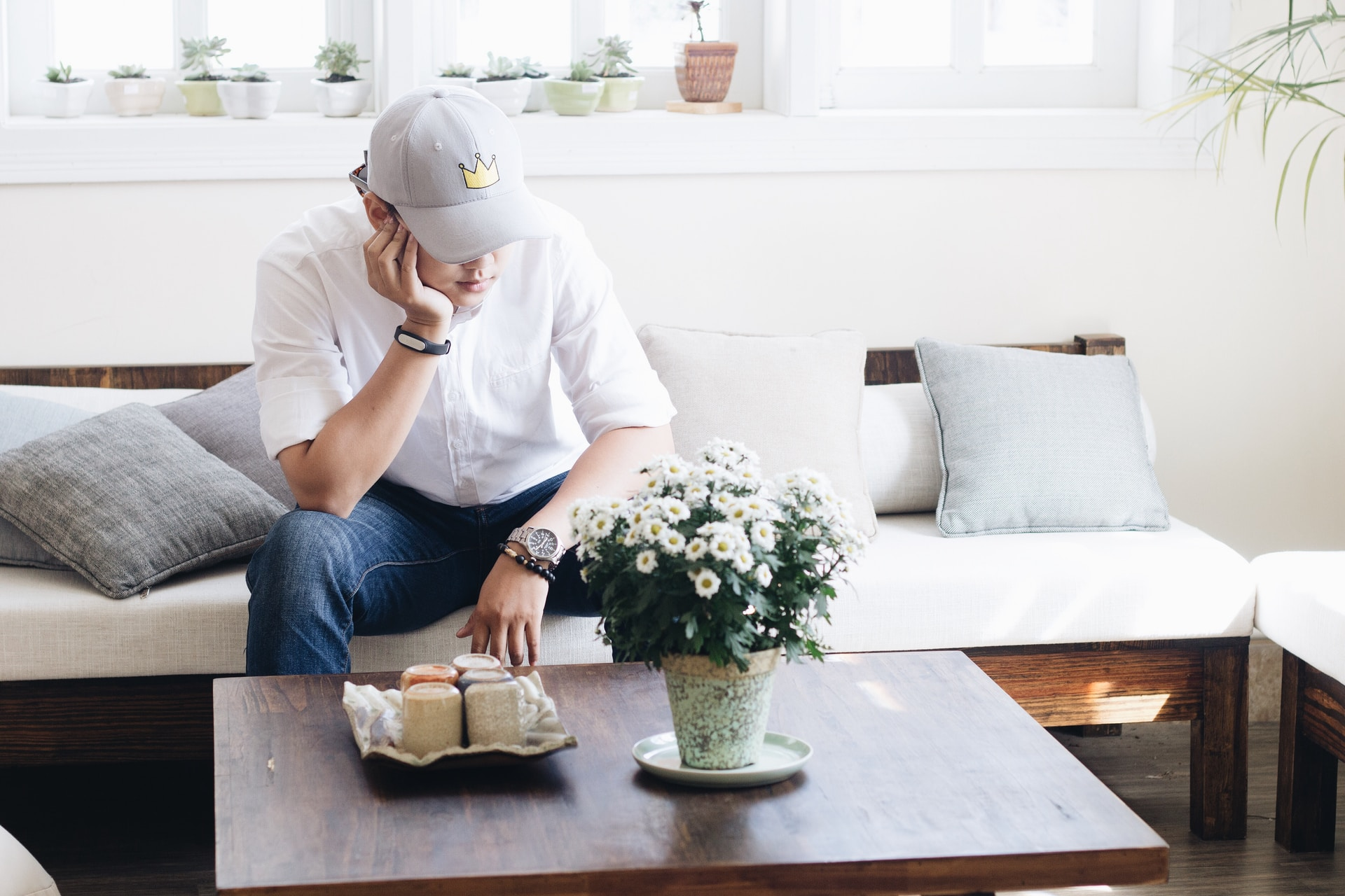 man sitting on white fabric sofa infront of coffee table inside the living room