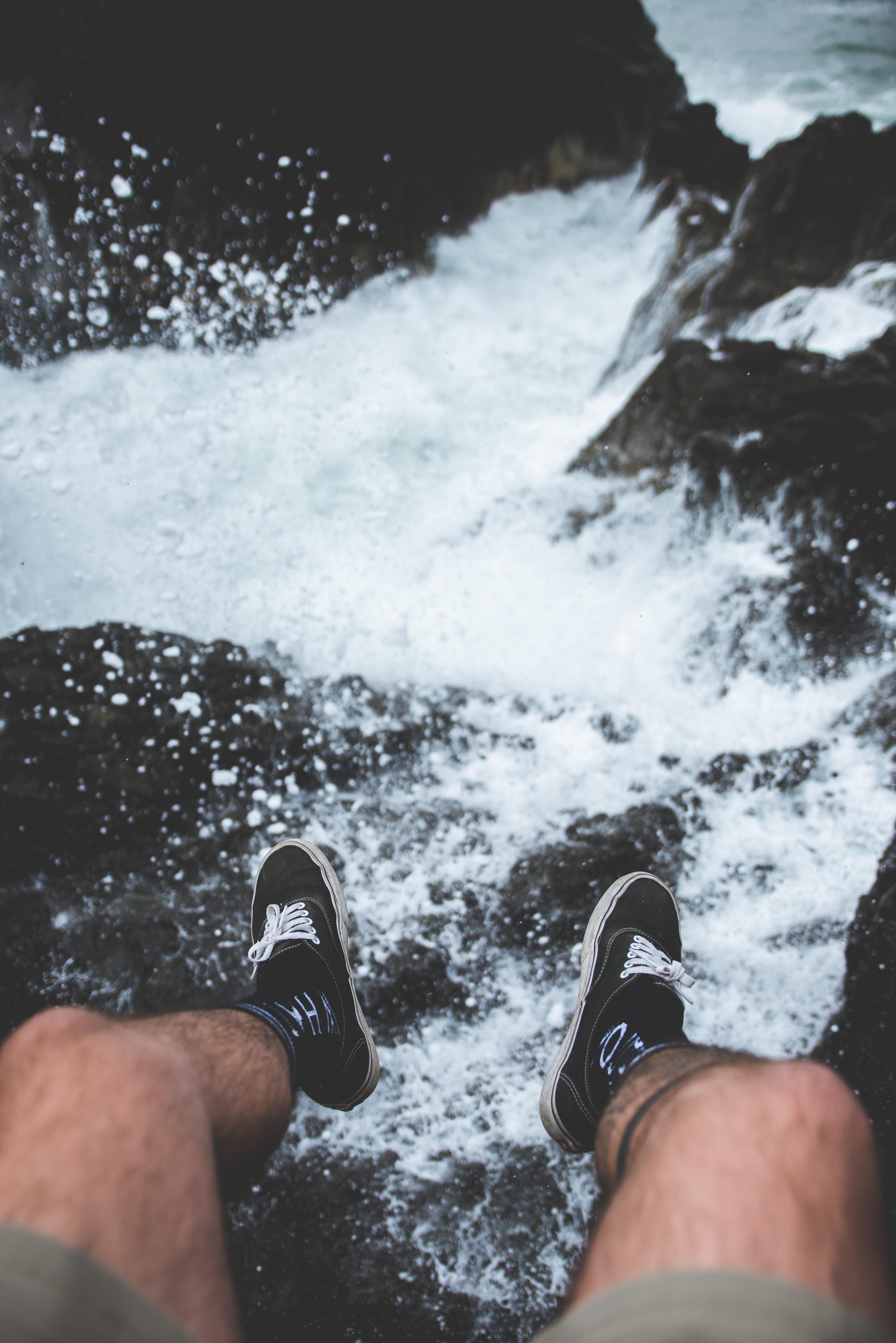 man sitting on rock near sea during daytime