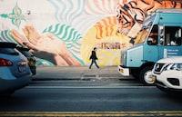 man walking on roadside during daytime