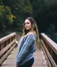 woman standing on bridge taking a photo