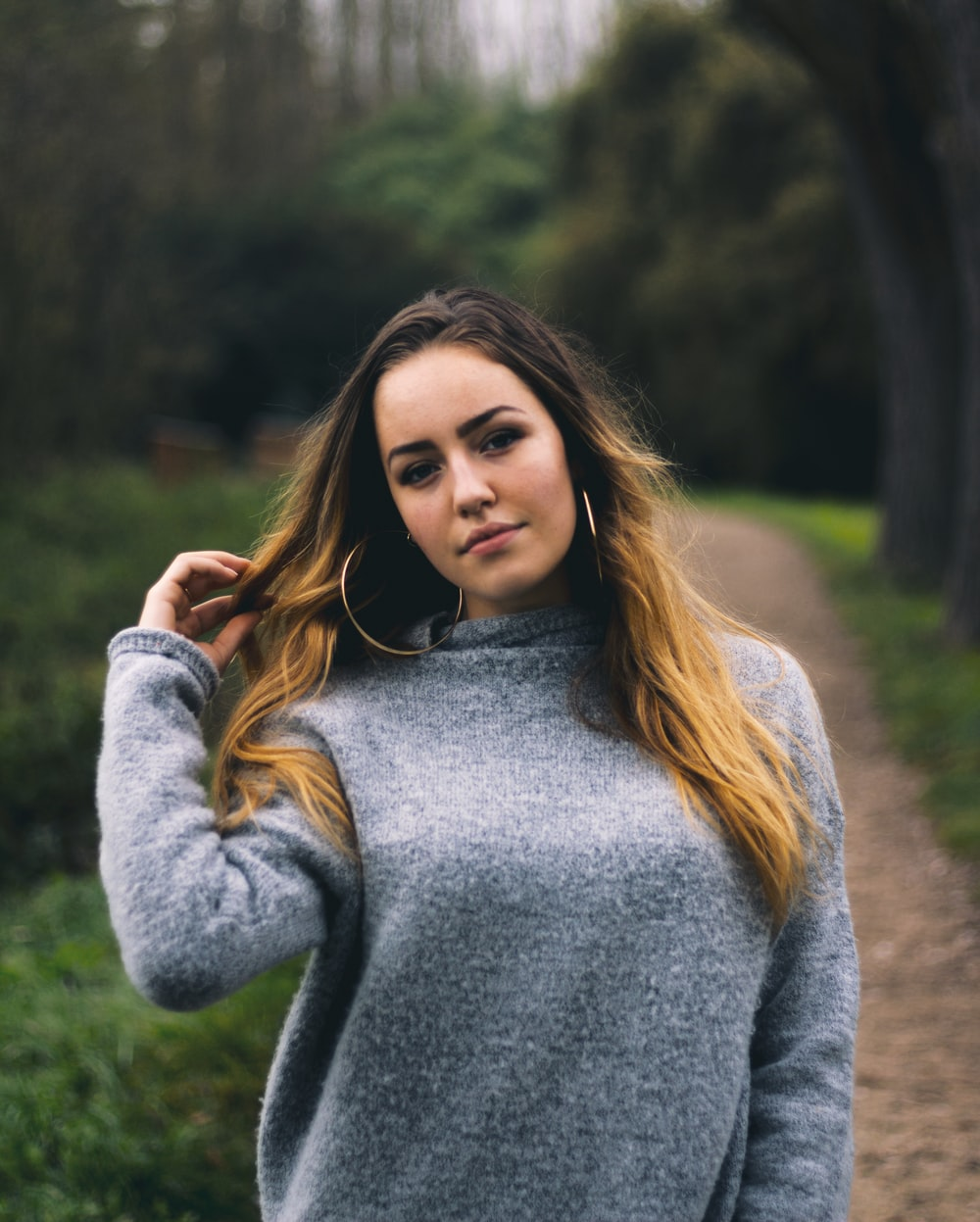 woman wearing gray knit sweater holding her hair
