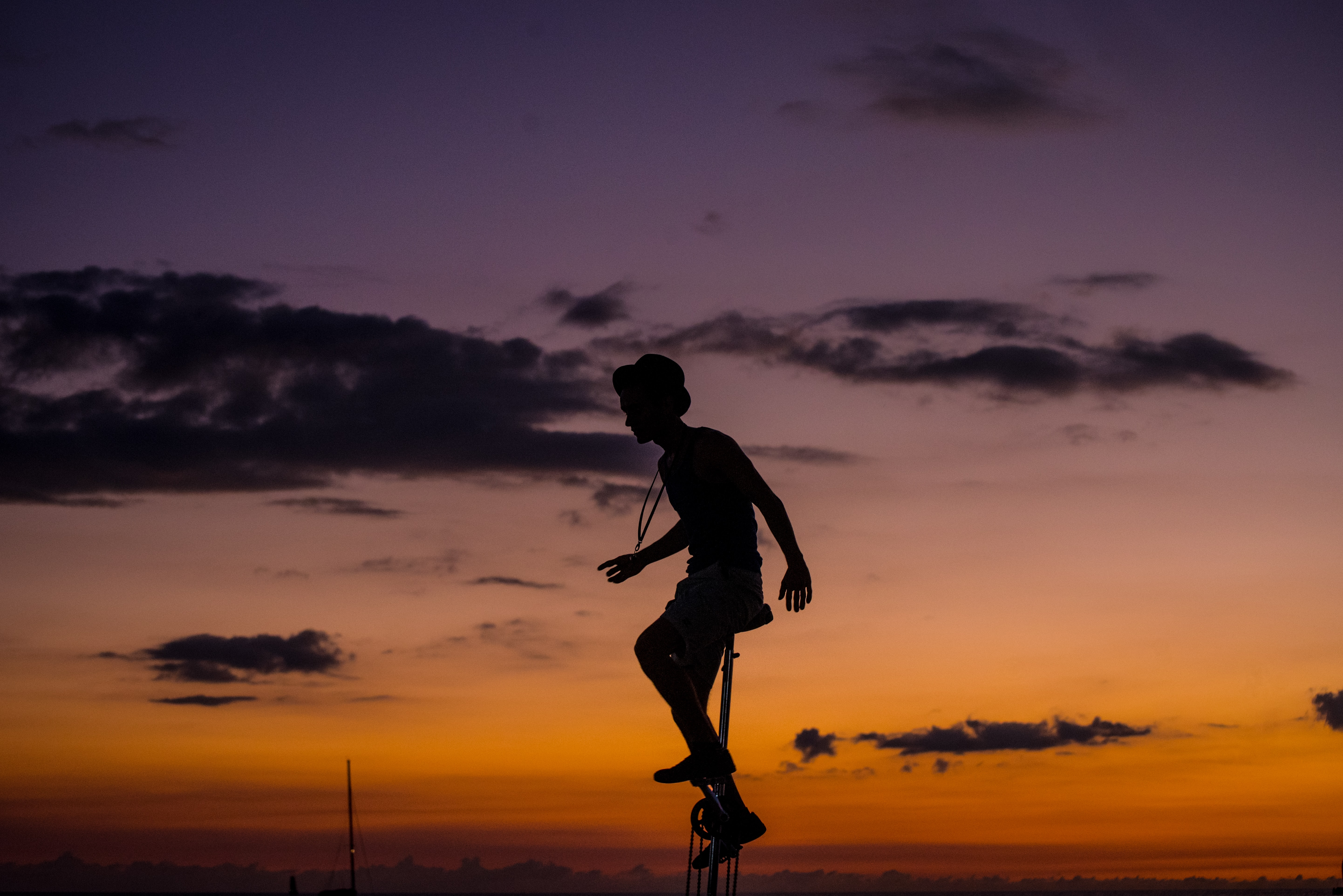 silhouette photo of man riding unicycle