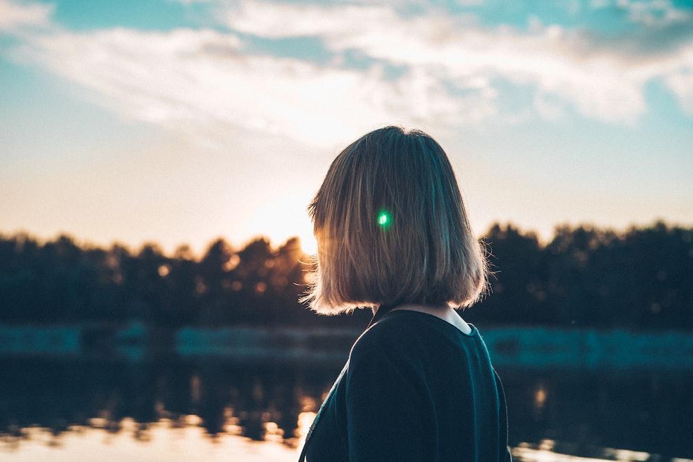 woman standing near lake during daytime