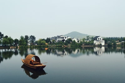 brown wooden boat on body of water overlooking houses by the shore at daytime china zoom background
