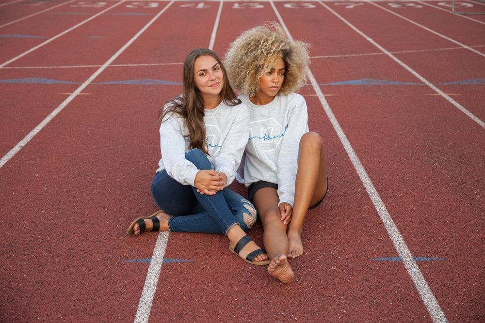 photograph of two woman seating on track field