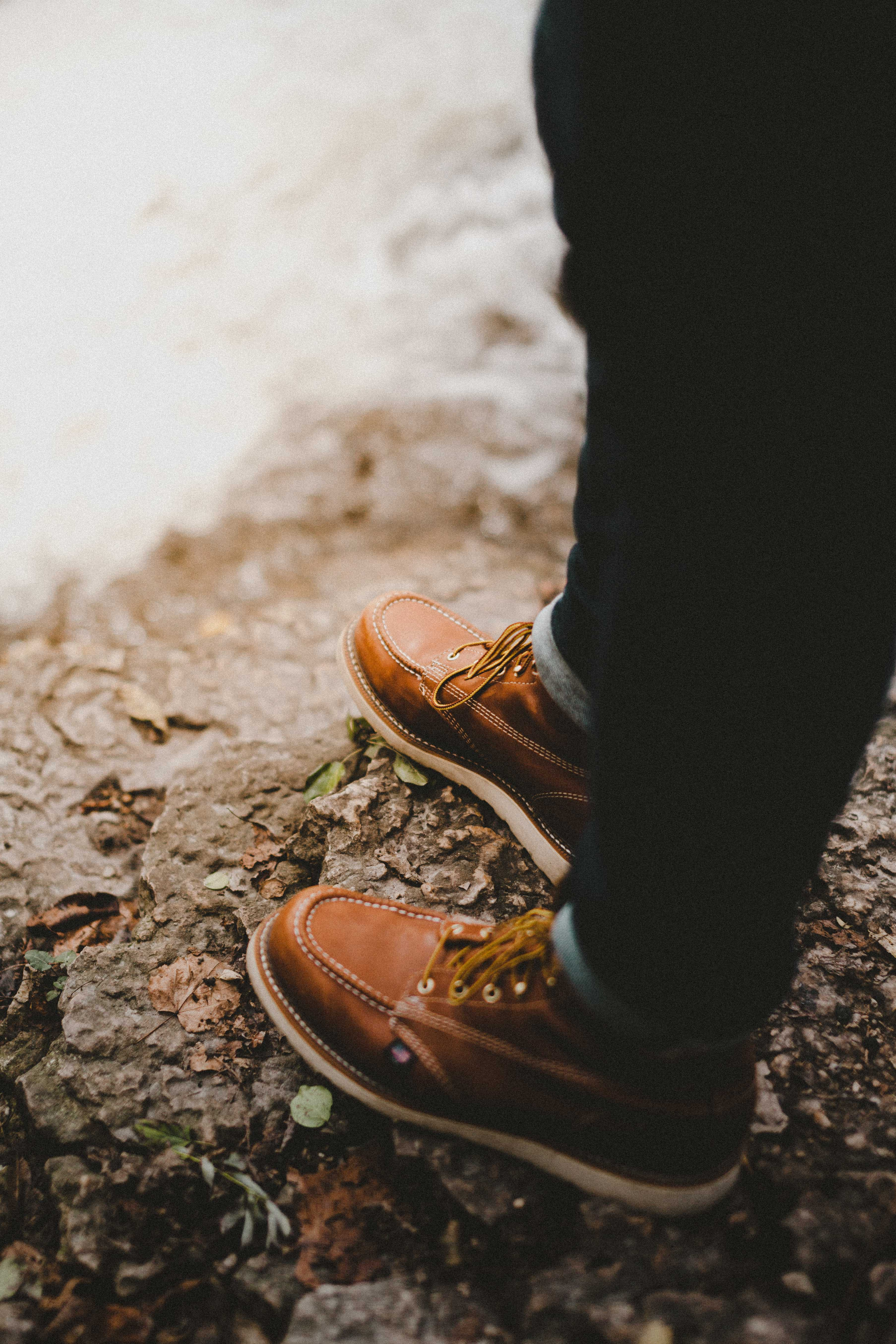 selective focus photography of person wearing brown lace-up shoes standing on rock