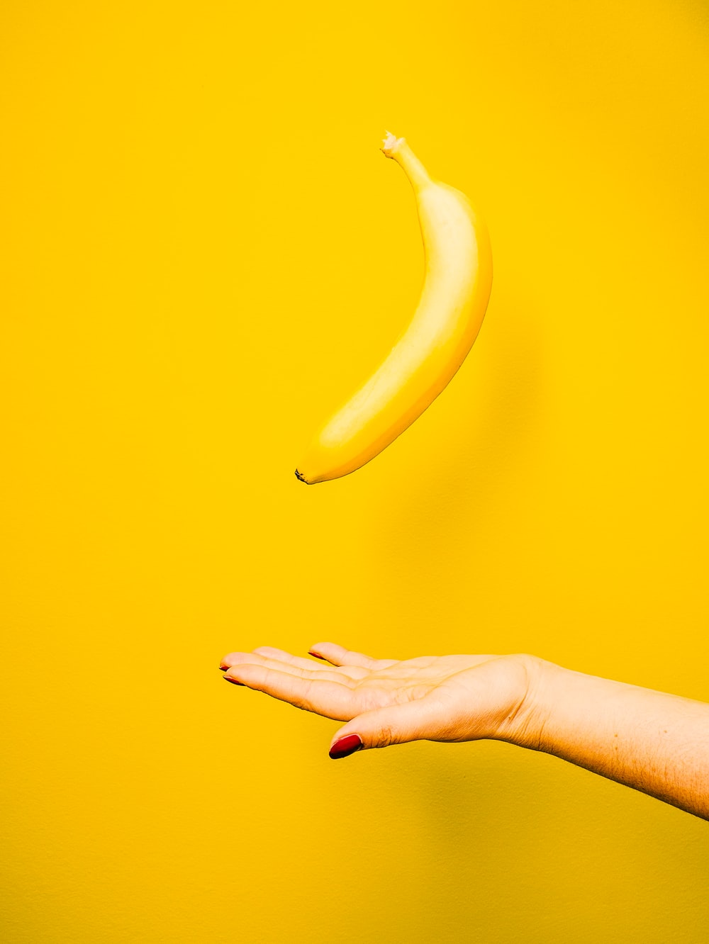 Photo Via: https://unsplash.com/photos/4krHo2fSil0, banana mid-air, yellow background.