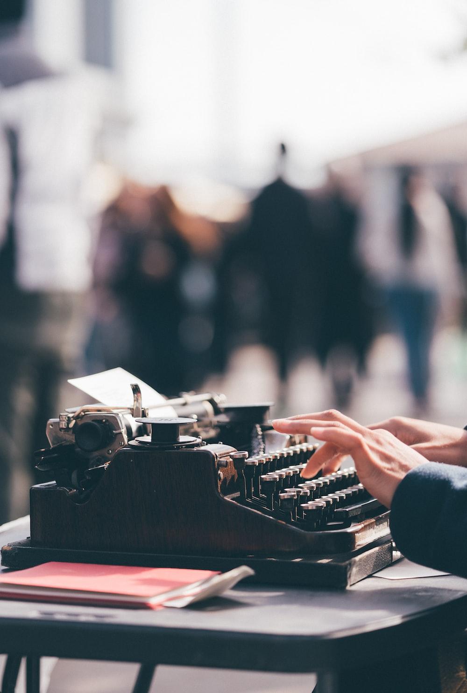 person using black typewriter